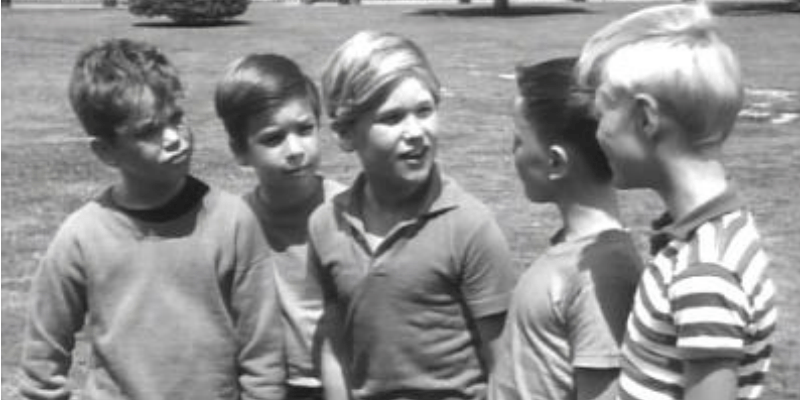 Kurt Russell in the center of young boys in Dennis the Menace.