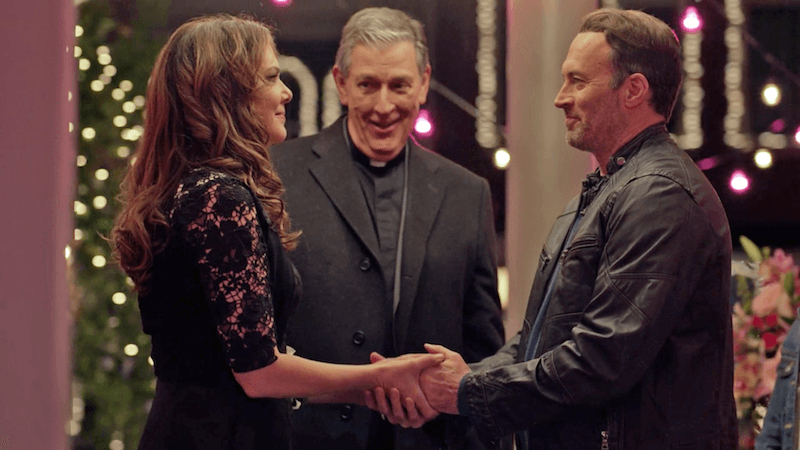 A man and a woman being married by a priest
