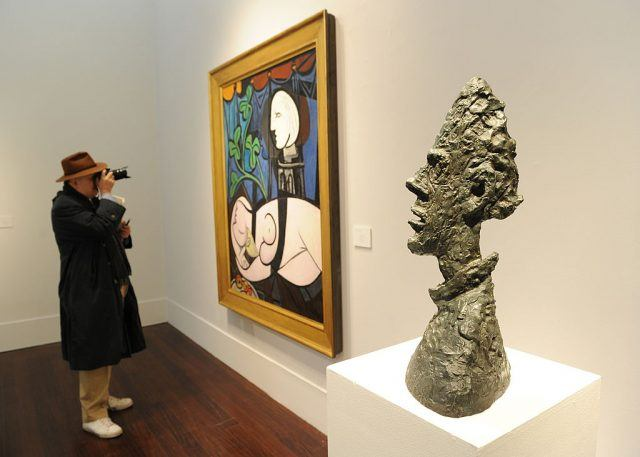 """A man photographs Pablo Picasso's """"Nude, Green Leaves and Bust"""""""