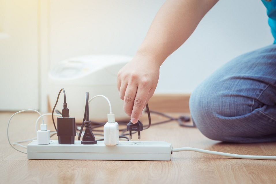 a man plugs several things into a power strip