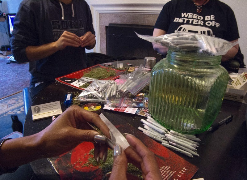 Members of the DC Marijuana Coalition roll joints at a table
