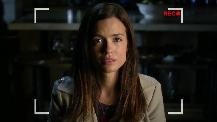 Torrey DeVitto as Melissa Hastings talking to a camera that is recording in a kitchen on Pretty Little Liars