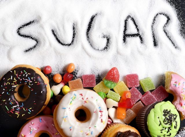 "Donuts and candy with sugar spread under it and the word ""sugar"" written over top"