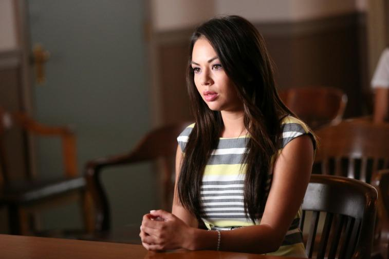 Janel Parrish as Mona Vanderwaal on Pretty Little Liars sitting at a table with her hands folded.