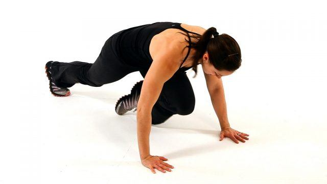 A woman does mountain climbers on a white floor.