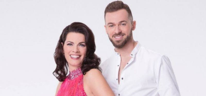 Nancy Kerrigan in a pink dress next to Artem Chigvintsev in a white shirt