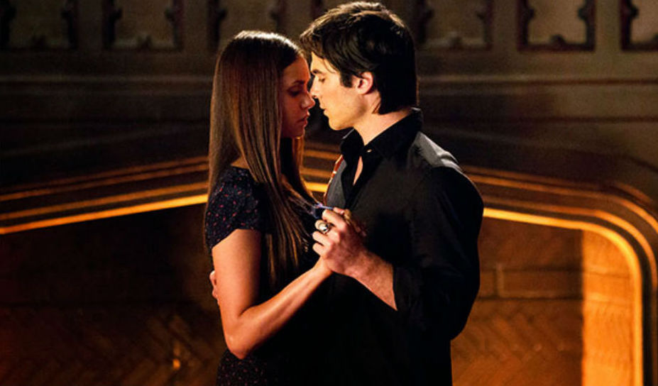 Damon and Elena are dancing in front of a fireplace on The Vampire Diairies.