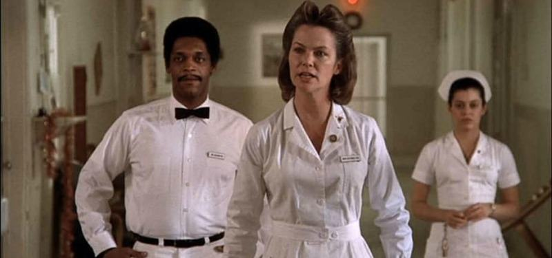 Nurse Ratched angrily walks down the hospital hall with two other workers behind her.