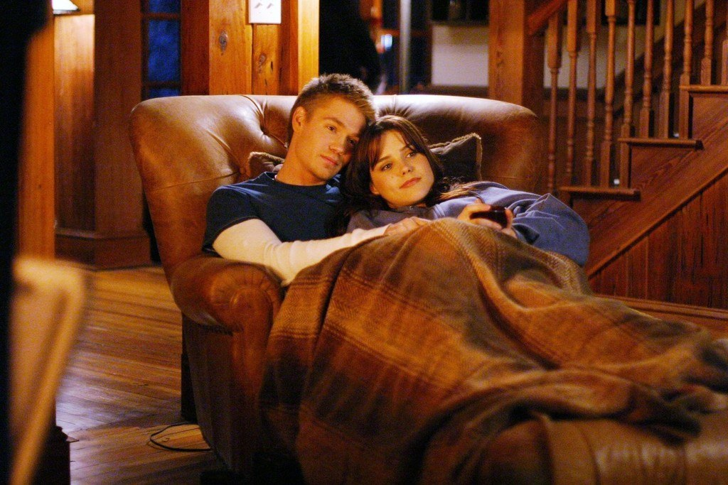 Lucas and Brooke cuddling on a chair under a blanket.