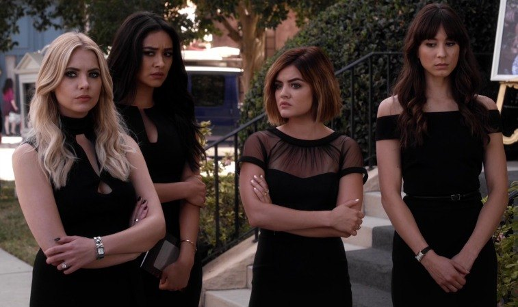 Four girls in black dresses stand outside next to steps looking concerned