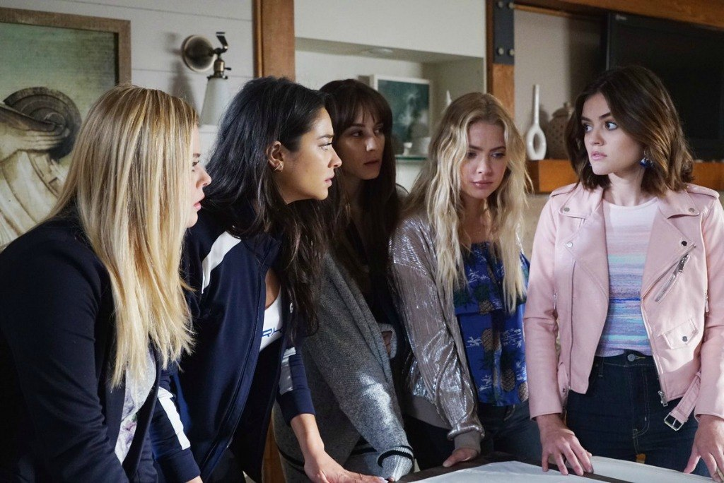 Five girls looking at one another and standing over a table