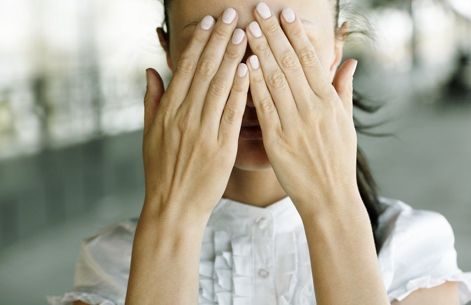 Woman with hands covering the eyes