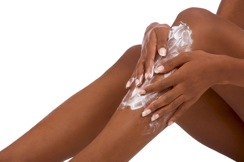 Woman applying lotion to her legs.
