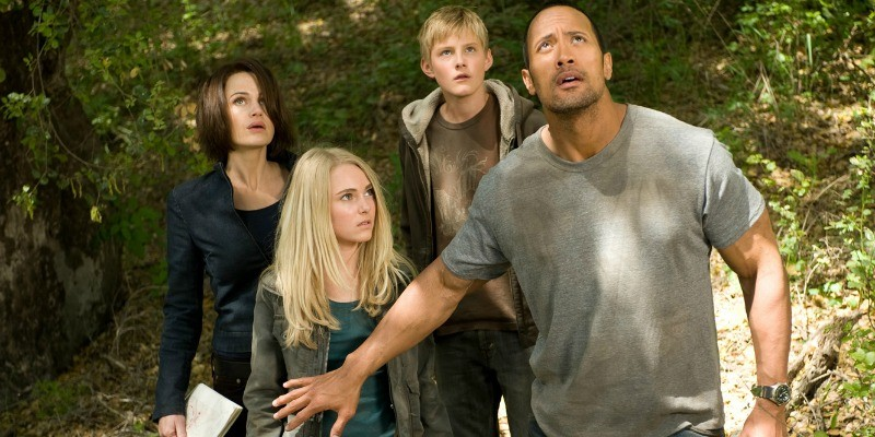 Dwayne Johnson is looking up at the sky as he has his arm out stopping the rest of the group.
