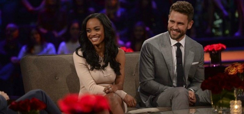 Rachel Lindsay and Nick Viall sitting next to each other and smiling on Women Tell All