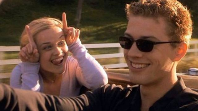 Reese Witherspoon laughing with her fingers pointed up, while Ryan Phillippe drives