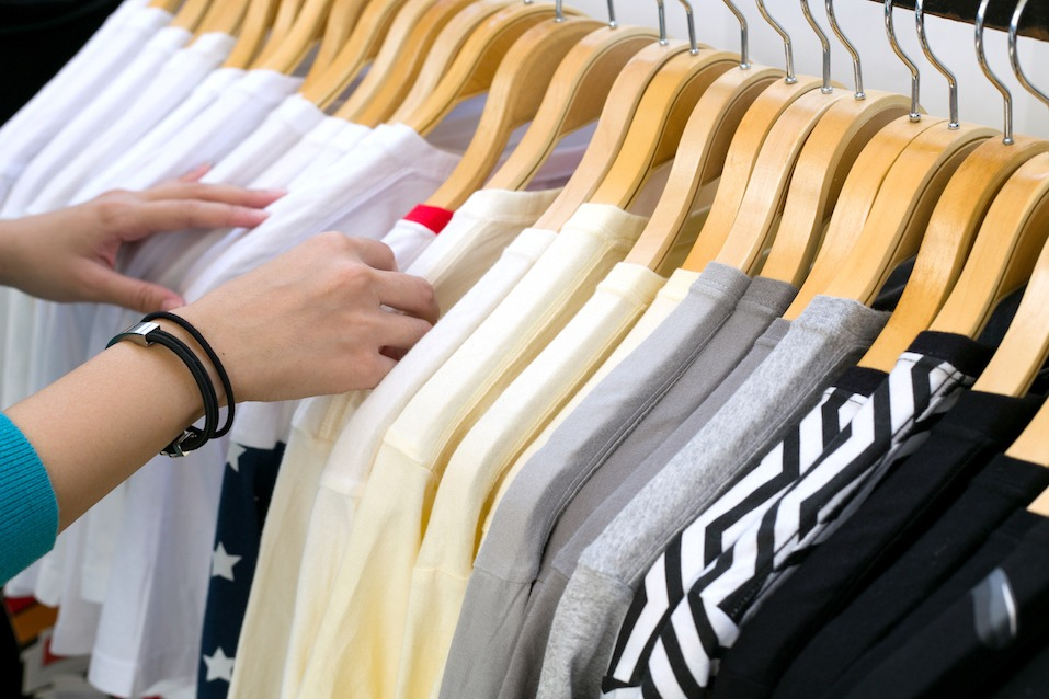 Young woman looking at new shirts while shopping in store