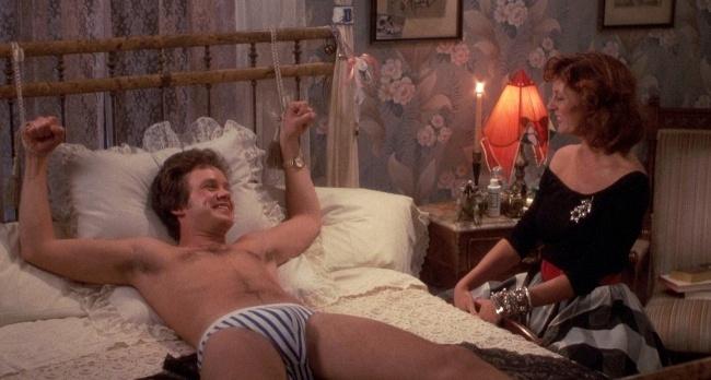 Tim Robbins tied to a bed, with Susan Sarandaon sitting next to him