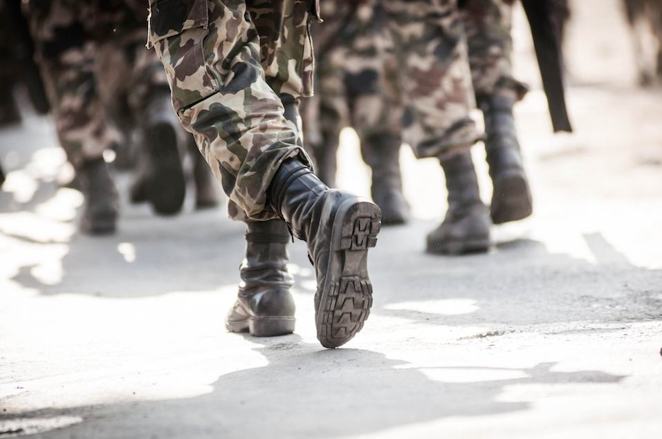 military members marching wearing combat boots and camo
