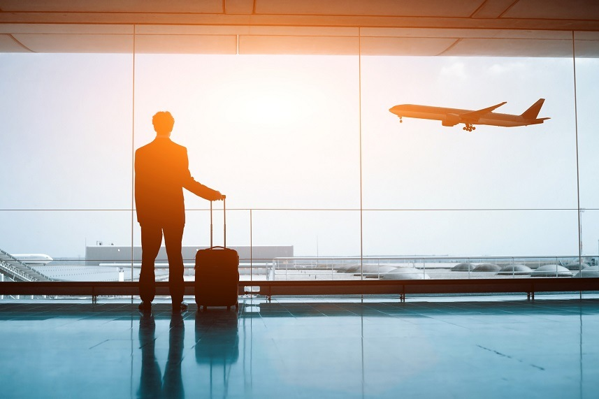 man with luggage at airport looking at airplane