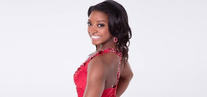 Simone Biles posing in a red dancing outfit for the show