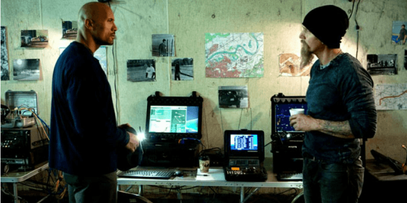 Dwayne Johnson and another man are talking in a room of computers in Snitch.