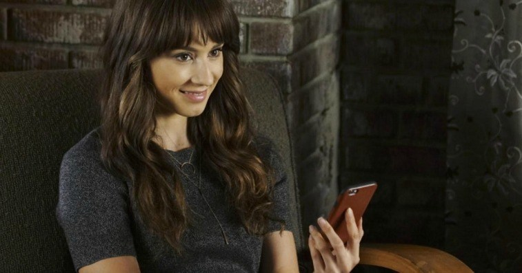 Brunette young woman in a gray short-sleeved sweater against a brick wall holding a smart phone