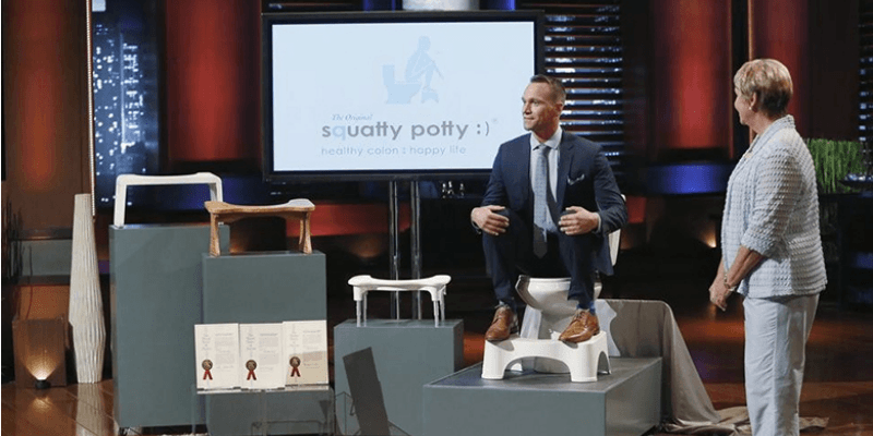 Bobby Edwards is sitting on a Squaty Potty in a suit on Shark Tank.