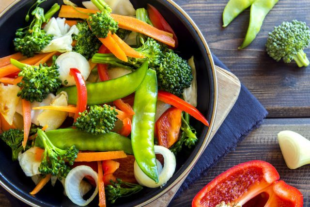 Healthy stir-fried vegetables in a pan on a table.
