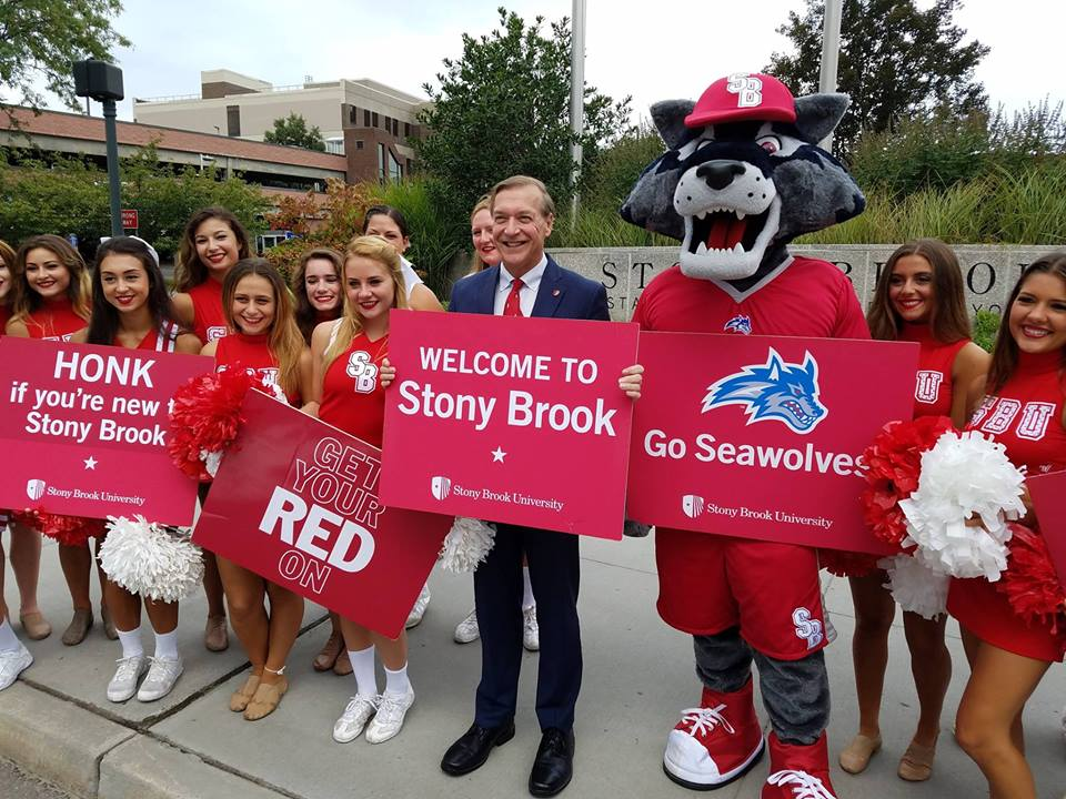 Stony Brook University students hold up welcome signs