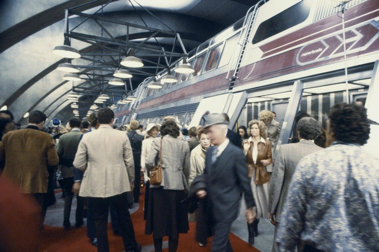 A crowd of passengers getting off a large train in a station