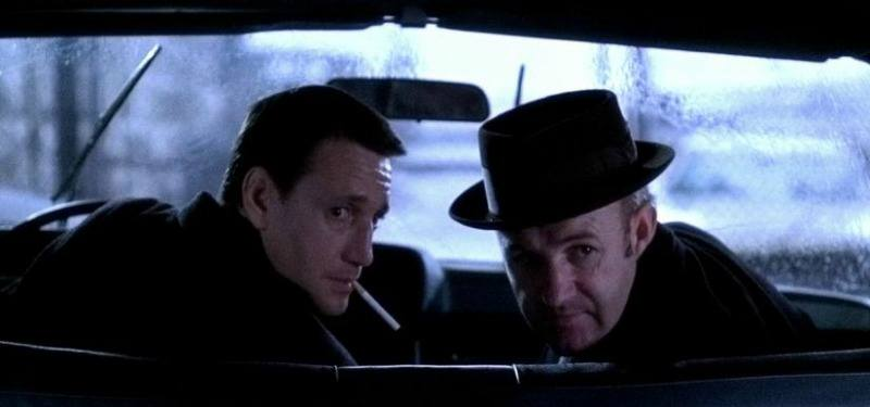 Jimmy and Buddy look back in a car in The French Connection.