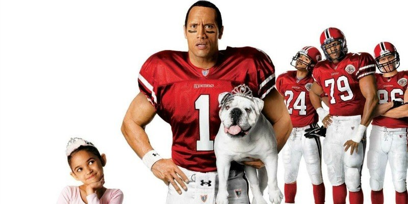 Dwayne Johnson poses in a football uniform holding a dog. A little girl is smiling on his left and his football teammates are on his right.