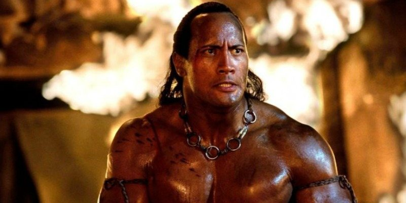 The Scorpion King is shirtless in front of fire.