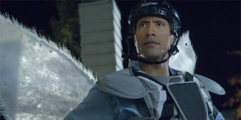 Dwayne Johnson has a chest and shoulder pads on and is wearing wings and a helmet.
