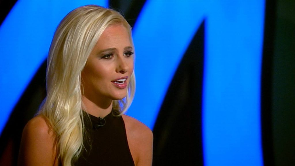 Tomi Lahren looks to her right sitting at a news desk