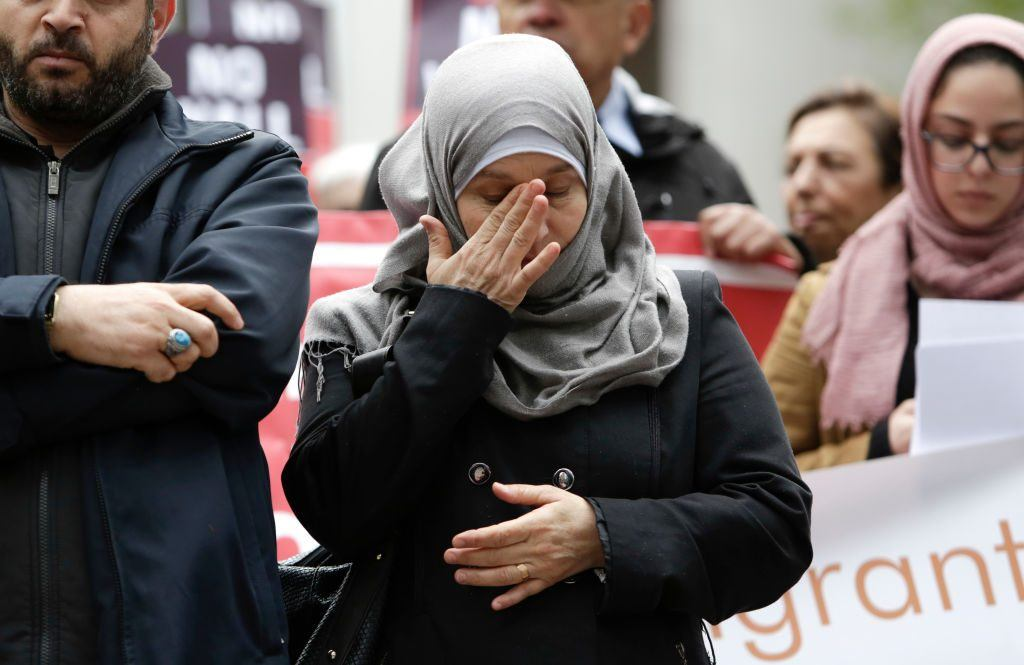 A Syrian refugee wipes her eyes as her husband tells their story to a group protesting President Donald Trump's revised travel ban