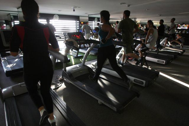 Men and women run on treadmills at a fit