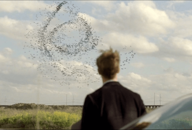 Birds swirl in a curled pattern as Rust Cohle watches in a scene from the first season of HBO's 'True Detective.'