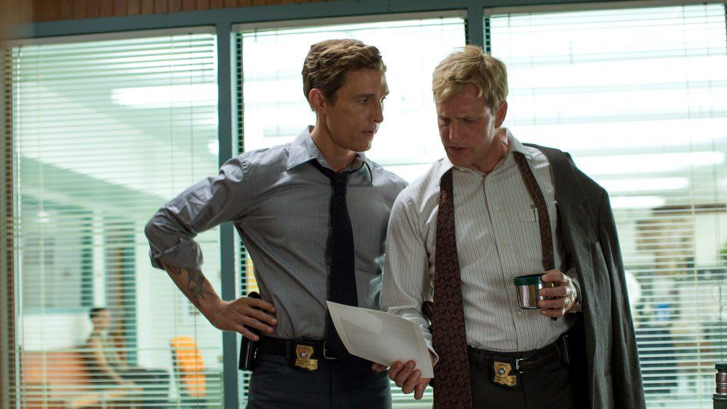 Matthew McConaughey and Woody Harrelson stand next to each other and look down at a piece of paper in True Detective Season 1 in an office wearing ties