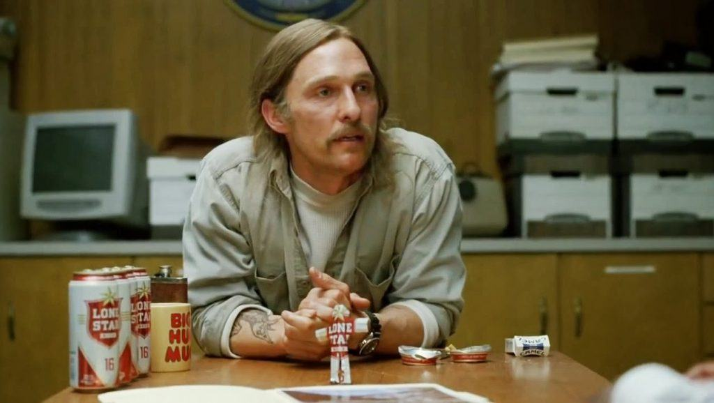 Matthew McConaughey sitting at a table containing beer and cigarettes in True Detective