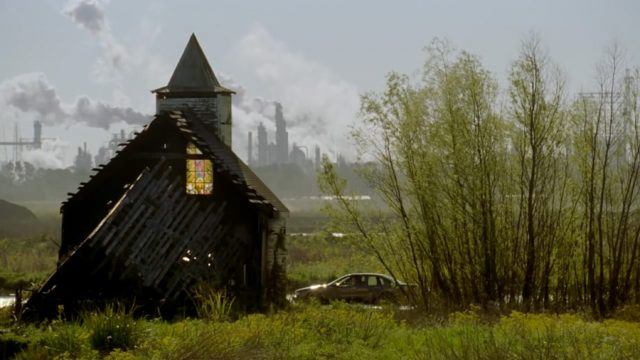 Rust and Marty's car drives past a factory and a dilapidated church in rural Louisiana in a scene from Season 1 of 'True Detective.'