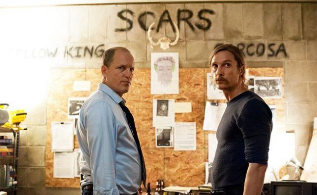 Marty and Rust stand in front of a wall of evidence, which includes drawings, a skeleton of a head with antlers, and the words 'Yellow King,' and 'Scars.'