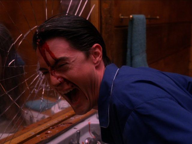 Dale Cooper laughs in front of a smashed bathroom mirror as blood runs down his face in the final scene of 'Twin Peaks'