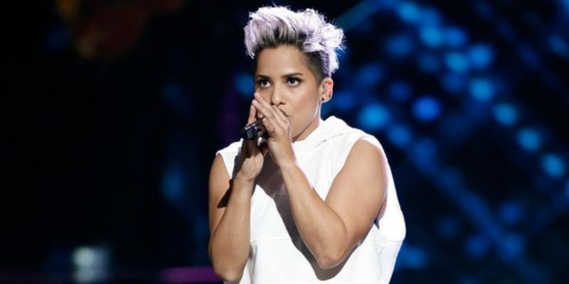 Vicci Martinez is holding the microphone very closely to her face as she sings.
