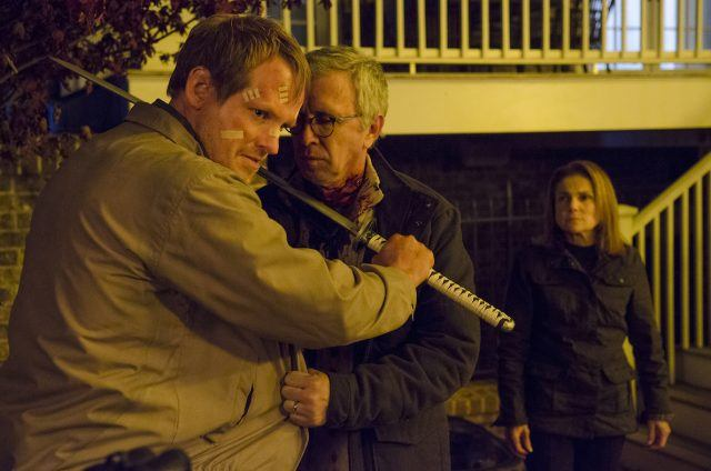 Pete holds a katana to Reg's throat as Deanna watches in a scene from 'The Walking Dead' fifth season finale.