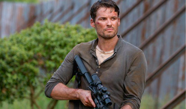 Spencer Monroe holds a gun as he walks through Alexandria in a scene from 'The Walking Dead'