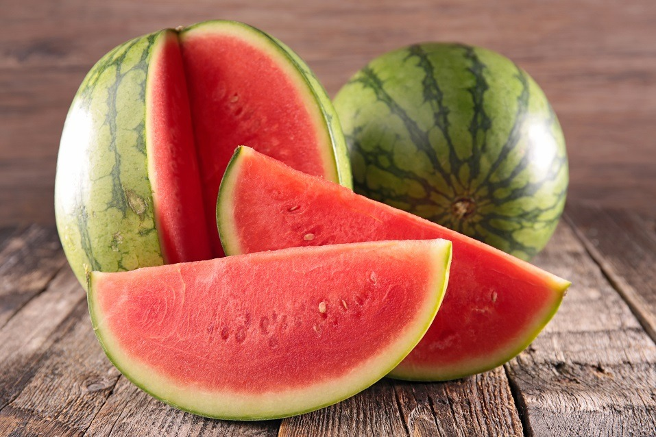 Watermelon sliced into sections and arranged on a wooden table.