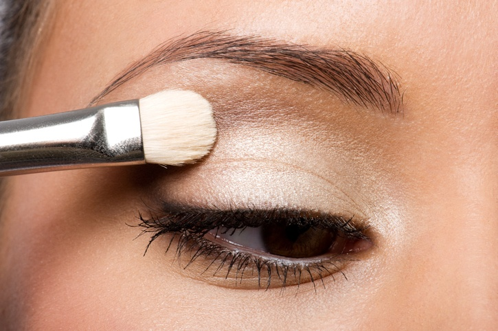 woman applying eyeshadow on eyelid