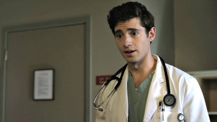 Wren Kingston on Pretty Little Liars brown-haired man in a lab coat wearing a stethoscope in a doctor's office